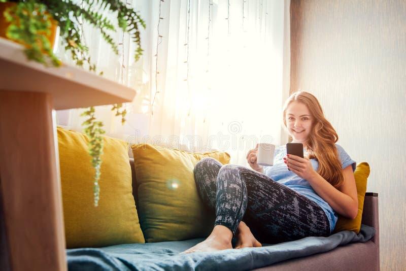 Café de consumición de la mujer joven que se sienta en la sala de estar fotos de archivo