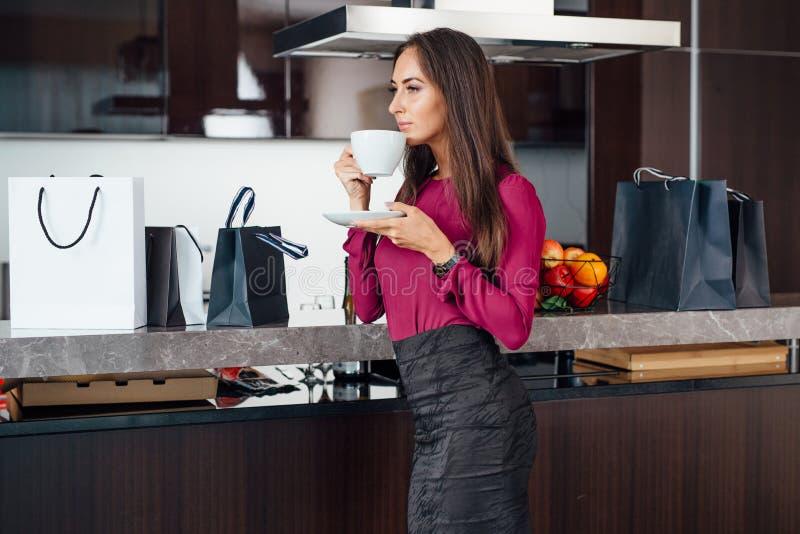 Café de consumición de la mujer latina joven con clase que se coloca en la cocina que se relaja después de hacer compras fotos de archivo