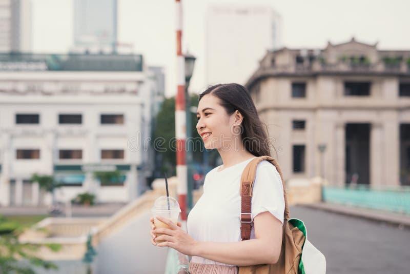 Café de consumición de la mujer linda joven en el puente en el fondo de la ciudad imagen de archivo