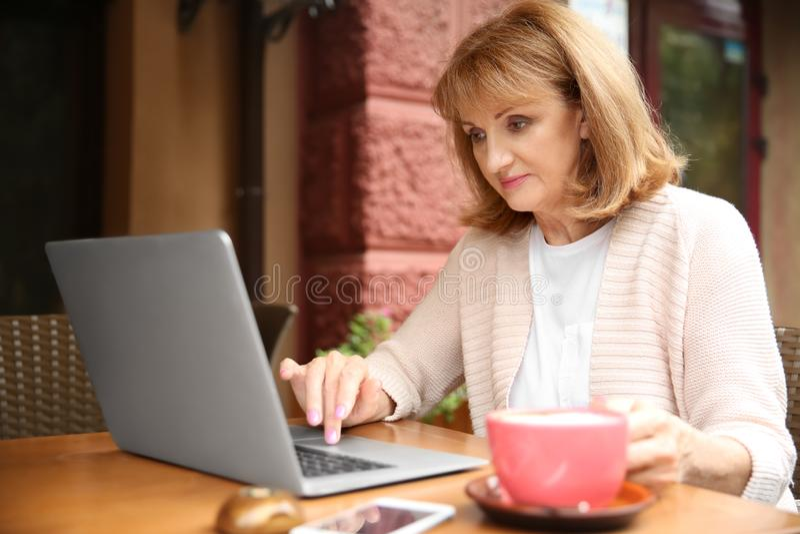 Café de consumición de la mujer madura hermosa y trabajo en el ordenador portátil en café fotografía de archivo