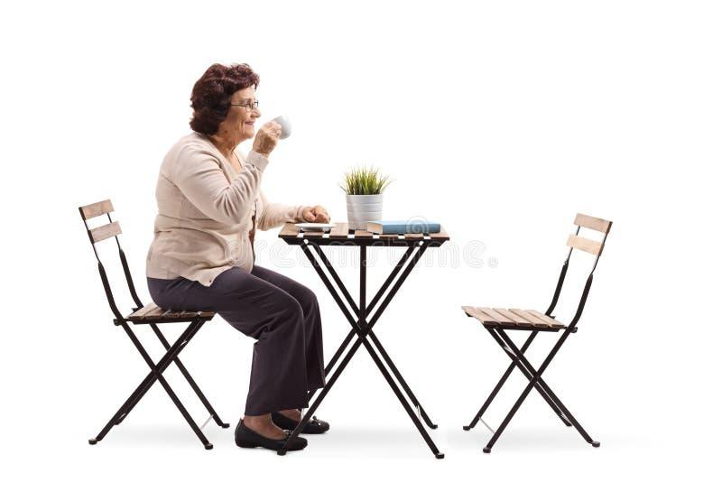 Café de consumición de la mujer mayor en una tabla foto de archivo