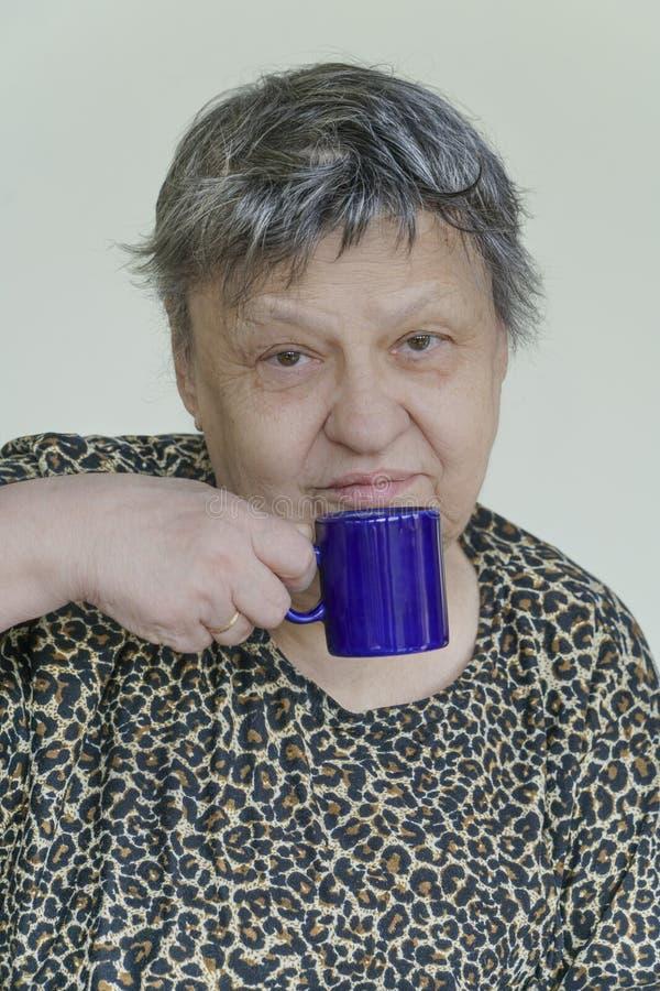Café de consumición de la mujer mayor preciosa de una taza azul fotografía de archivo libre de regalías