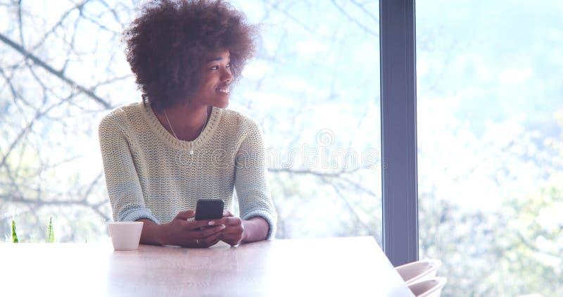 Café de consumición de la mujer negra y usar un teléfono móvil en casa imágenes de archivo libres de regalías