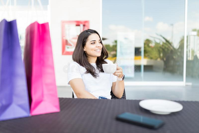 Café de consumición de la mujer relajada después de hacer compras imágenes de archivo libres de regalías
