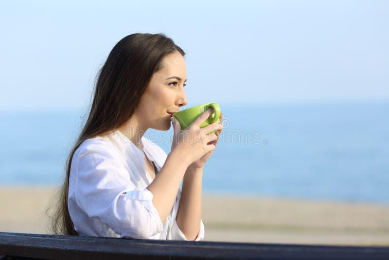 Café de consumición de la mujer y mirada lejos en la playa imagen de archivo