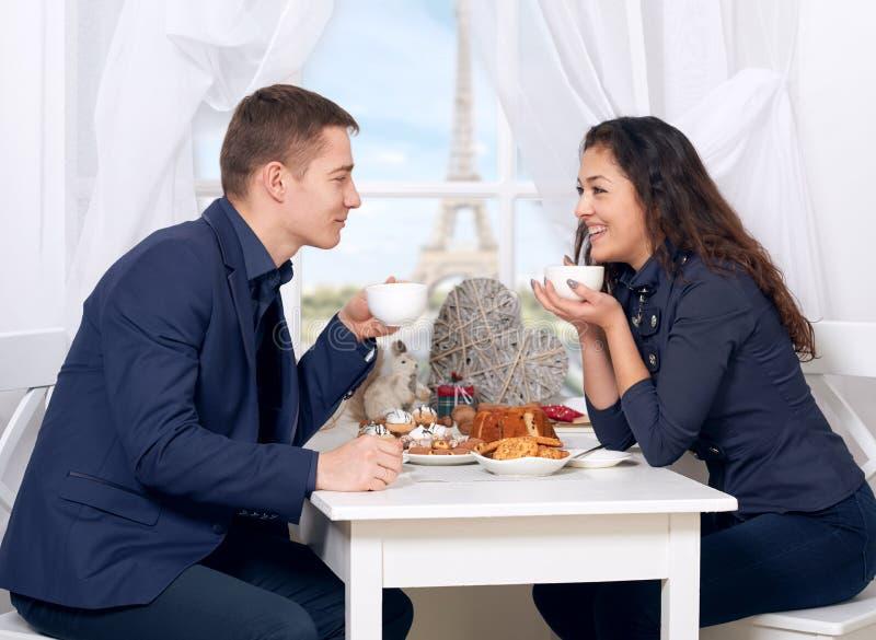 Café de consumición de los pares felices cerca de la ventana con vistas a la torre Eiffel - viaje y ame el concepto fotos de archivo