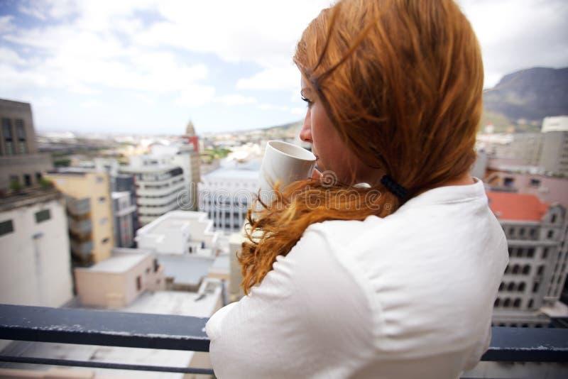 Café de consumición moreno atractivo en balcón imagen de archivo