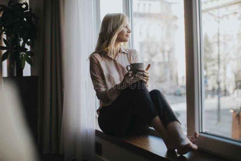 Café de consumición rubio de la mujer joven por la ventana foto de archivo libre de regalías
