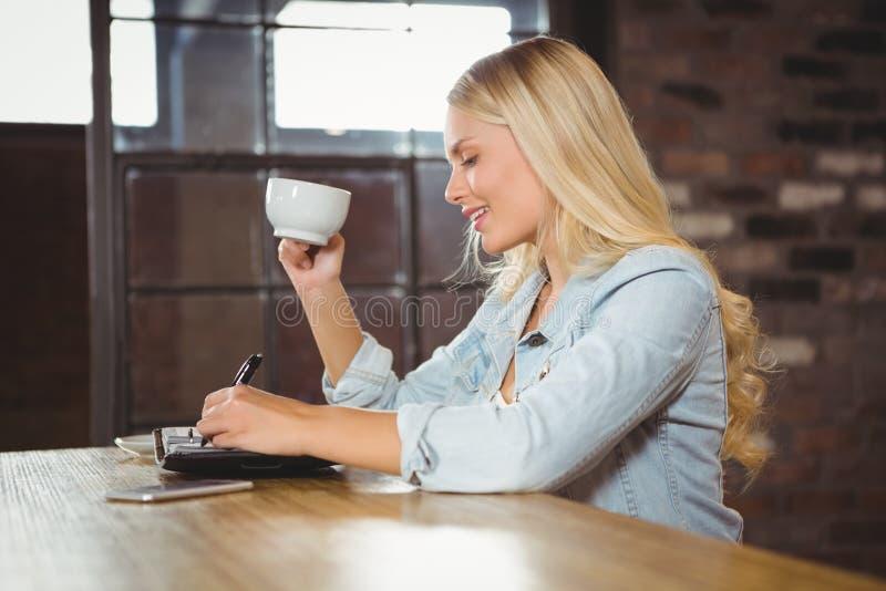 Café De Consumición Rubio Sonriente Y Escritura En Planificador Foto ...
