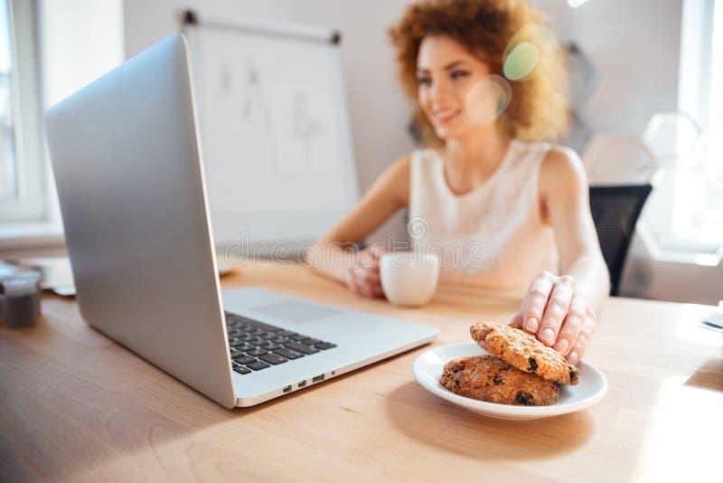 Café de consumición sonriente de la mujer de negocios con las galletas en lugar de trabajo fotografía de archivo