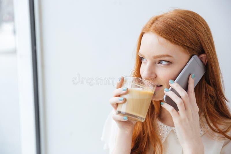 Café de consumición sonriente de la mujer y el hablar en el teléfono celular fotos de archivo