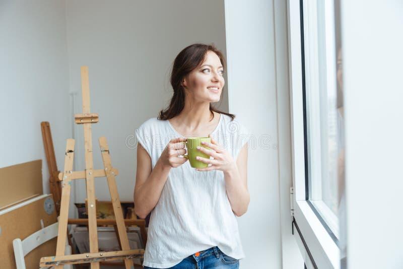 Café de consumición sonriente del artista bonito de la mujer en taller imagenes de archivo