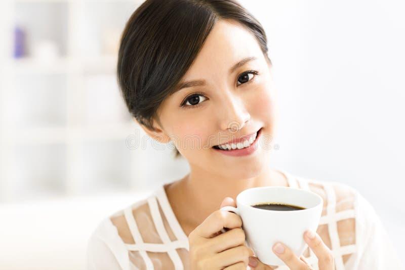 Café de consumición sonriente joven de la mujer por la mañana imagen de archivo