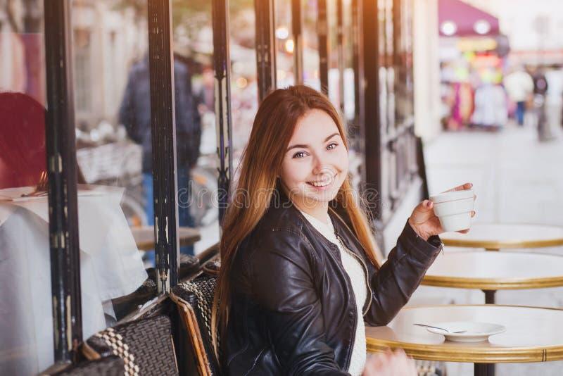 Café de consumición sonriente de la mujer en café de la calle en Europa fotografía de archivo