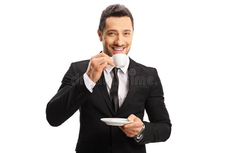 Café de consumición sonriente y mirada del café express del hombre de negocios joven de la cámara fotos de archivo