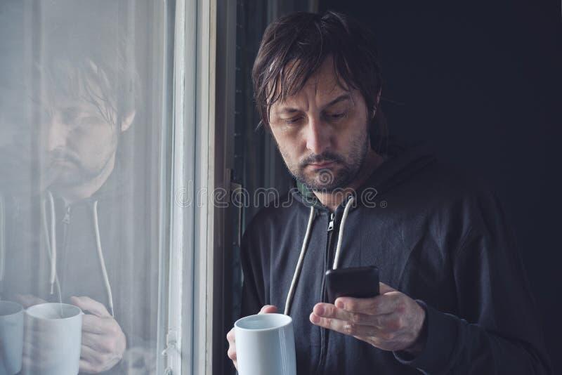 Café de consumición y lectura de SMS en el teléfono móvil por mañana fotografía de archivo