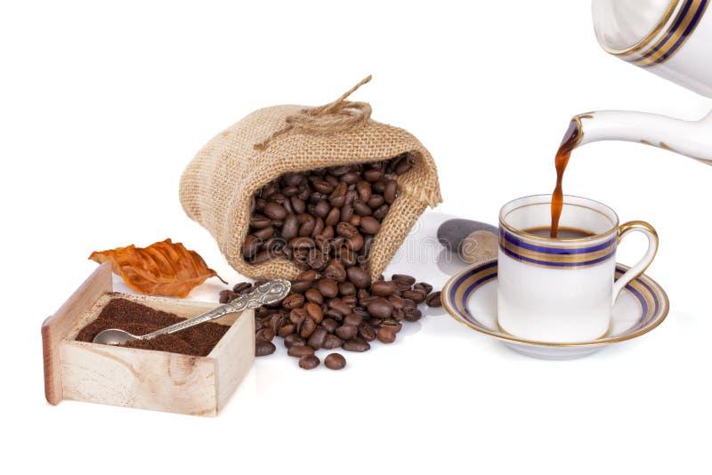Café de derramamento dentro com um potenciômetro do café em um copo velho isolado imagem de stock royalty free