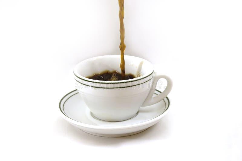 Café de derramamento em um copo   fotografia de stock