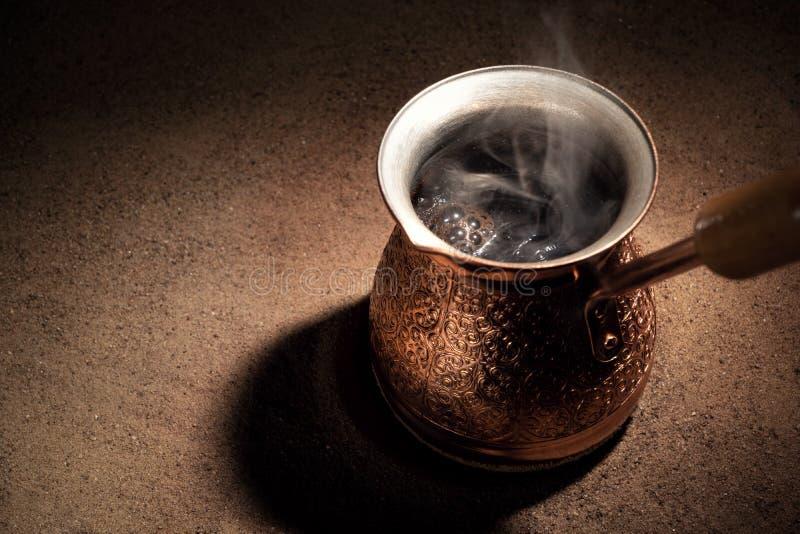 Café de ebullición en el café turco de cobre que prepara el pote fotos de archivo libres de regalías