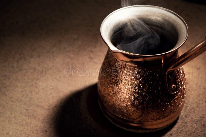 Café de ebullición en el café turco de cobre que prepara el pote fotos de archivo