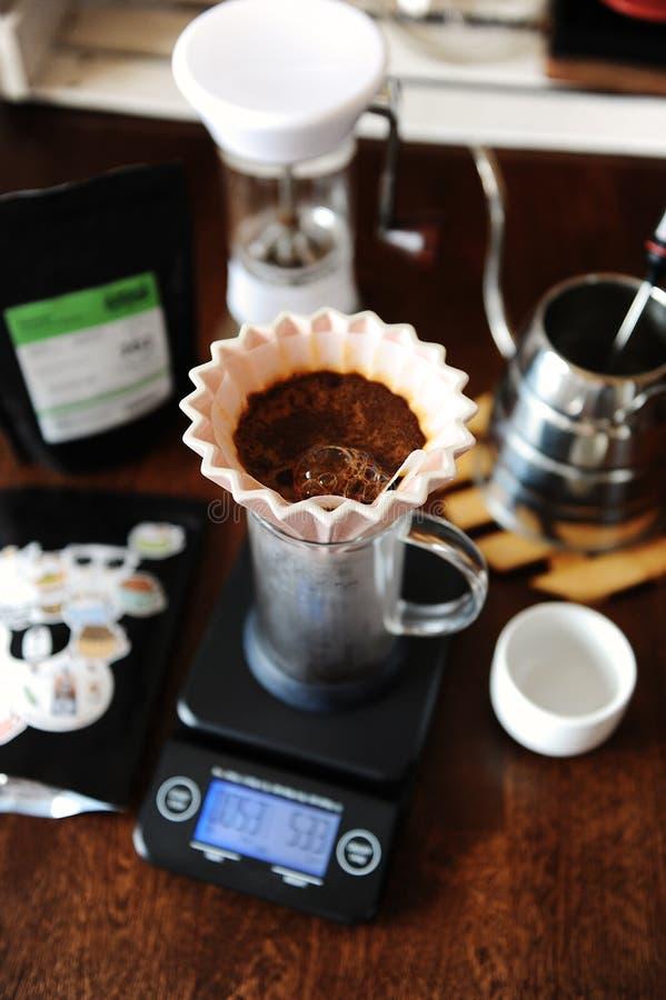 Café de floraison dans le dispositif d'écoulement en céramique rose d'origami avec le filtre de papier Brassage alternatif de caf image stock