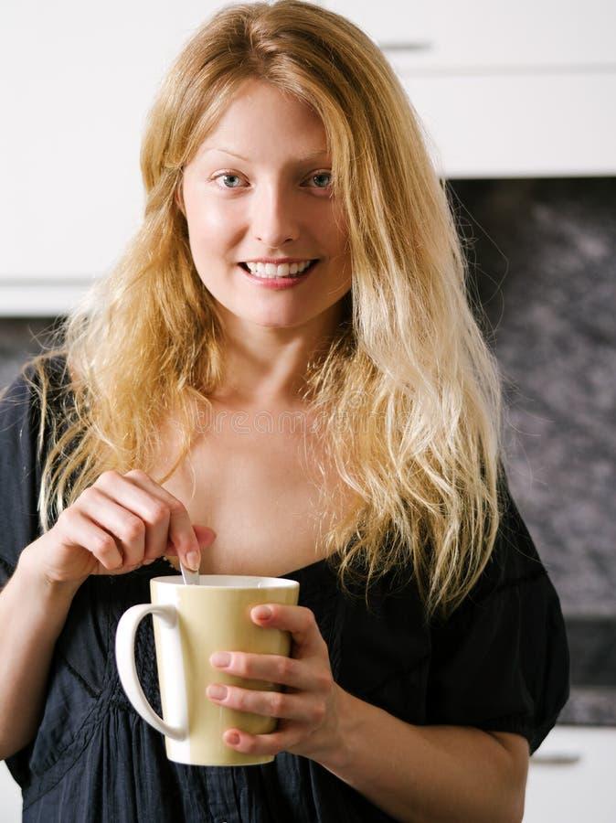 Café de goce femenino rubio en casa imagen de archivo libre de regalías