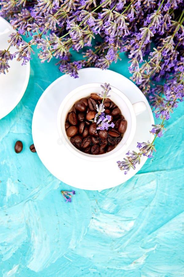 Café de grain en tasses et fleur de lavande sur le fond bleu d'en haut photo libre de droits