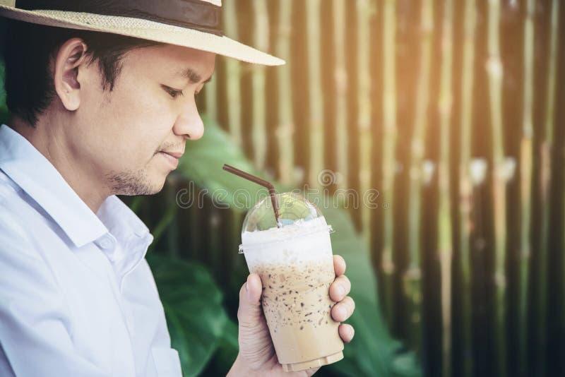 Café de hielo asiático casual de la bebida del hombre feliz en naturaleza foto de archivo