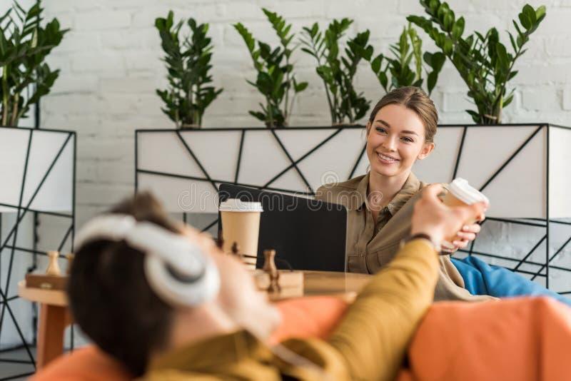 café de jeune homme et de femme et dispositifs potables d'utilisation tout en se reposant image stock