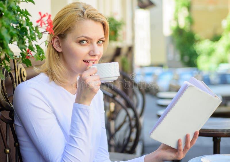 Café de la bebida de la muchacha mientras que libro leído del bestseller del autor popular Asalte combinación del café y del libr fotos de archivo