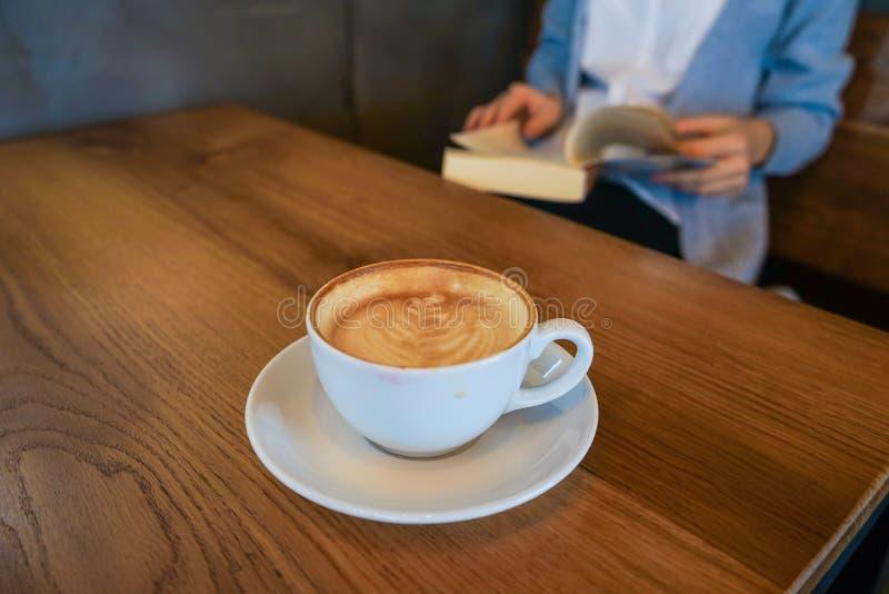 Café de la bebida de la mujer joven y leer un libro imagen de archivo libre de regalías