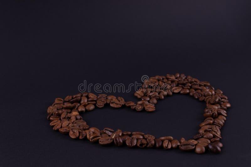 Café de la forma del corazón en el papel oscuro imagen de archivo libre de regalías
