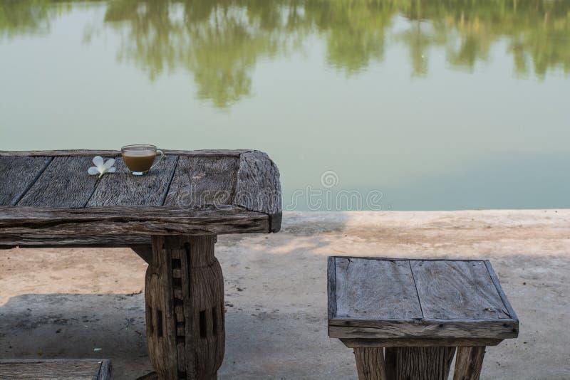 Café de la mañana en la tabla al lado del agua imágenes de archivo libres de regalías