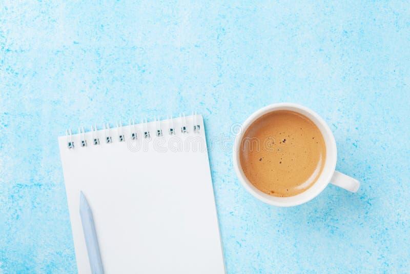 Café de la mañana, lápiz y cuaderno limpio en la opinión de sobremesa en colores pastel azul estilo plano de la endecha Concepto  imagen de archivo