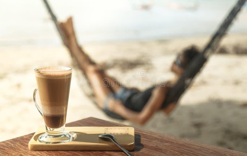 Café de la moca en una taza de cristal, en una tabla de madera foto de archivo