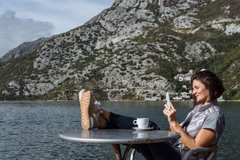 Café de la mujer joven y smarphone de consumición con por la mañana a fotografía de archivo