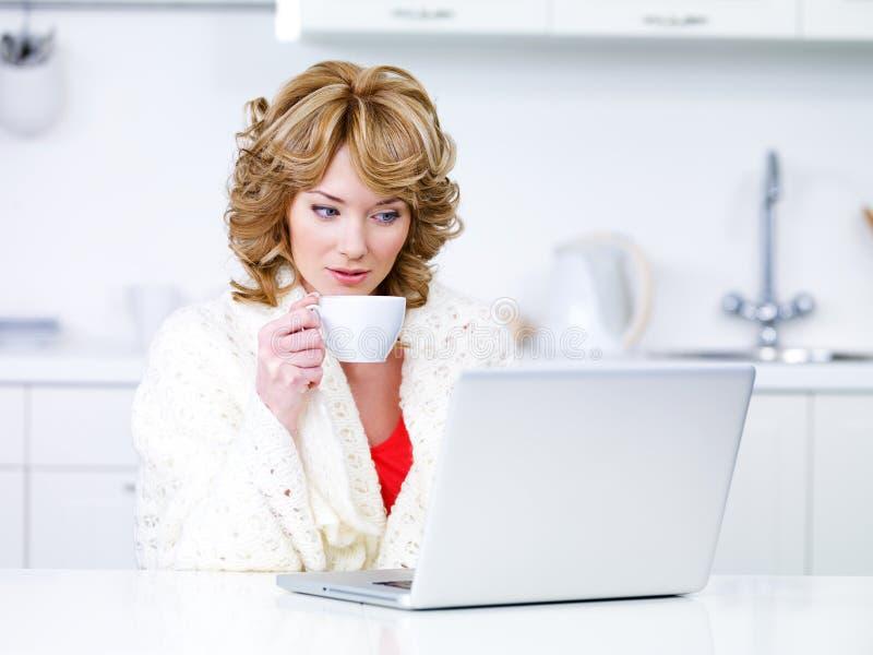Café de la mujer y computadora portátil de consumición con fotos de archivo libres de regalías