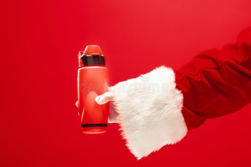 Café de la Navidad La mano de Papá Noel que sostiene el termo de cofee aislado en un fondo rojo con el espacio para el texto fotos de archivo