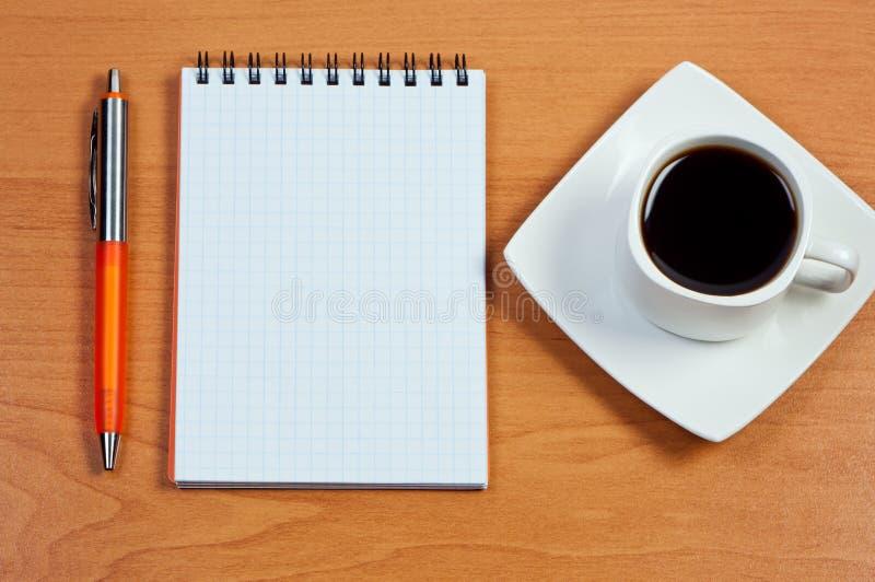 Café de la pluma, del cuaderno y de la taza en el vector. foto de archivo libre de regalías