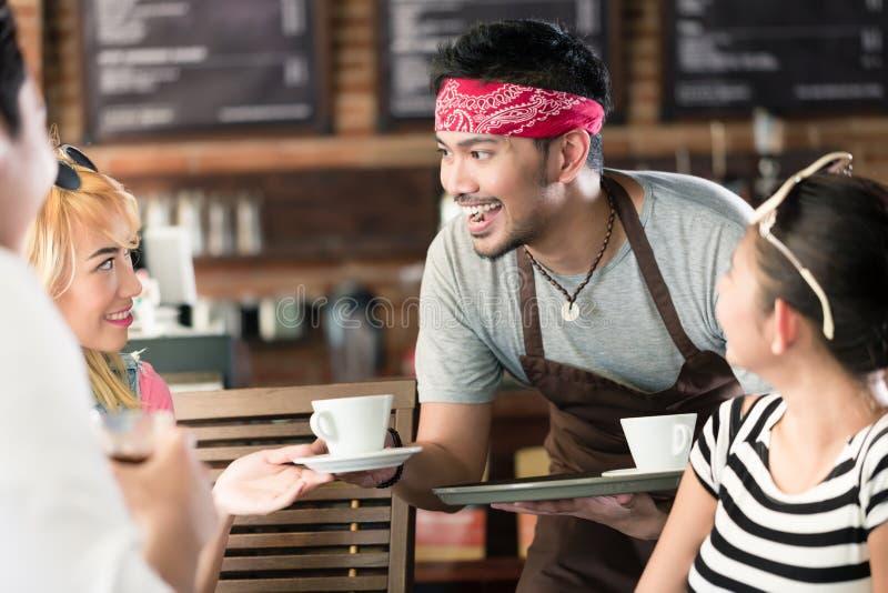 Café de la porción del camarero en café asiático a las mujeres y al hombre imagen de archivo