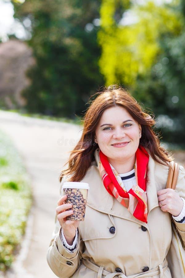Café de marche et potable de jeune femme en parc avec fleurir W image libre de droits
