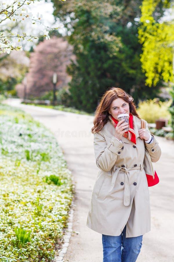 Café de marche et potable de jeune femme en parc avec fleurir W image stock