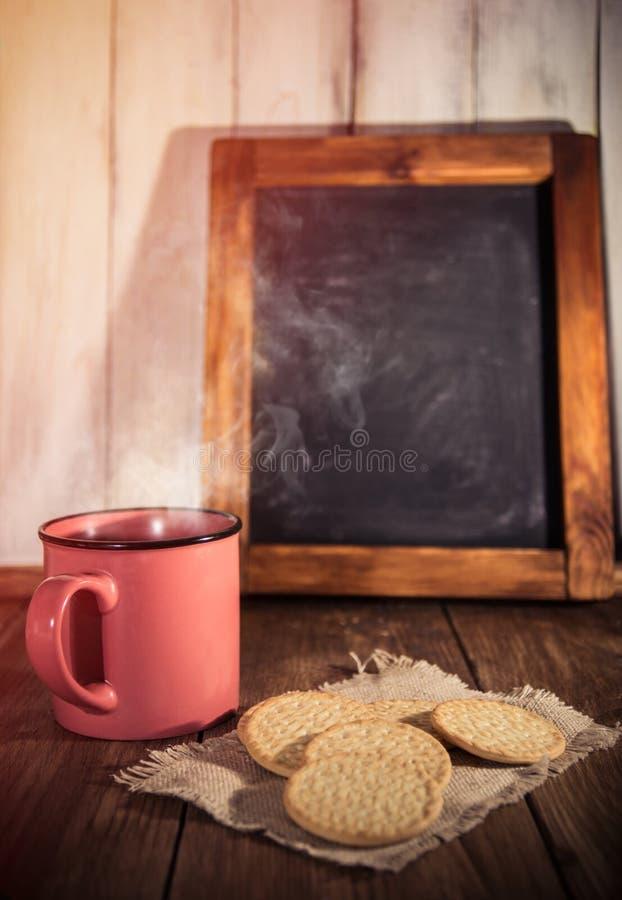 Café de matin avec des certains biscuits et tableau noir en bois âgé sur le fond rustique photographie stock