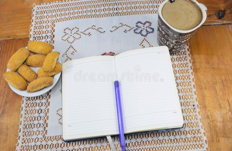 Café de matin avec du lait et des biscuits sur une table en bois, carnet, journal intime image libre de droits