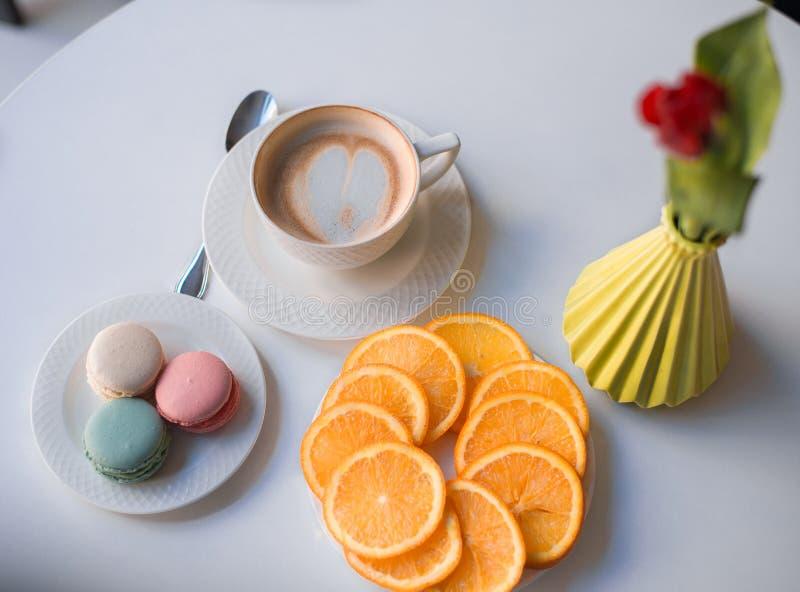 Café de matin avec les macarons et l'orange sur la table avec la fleur images stock