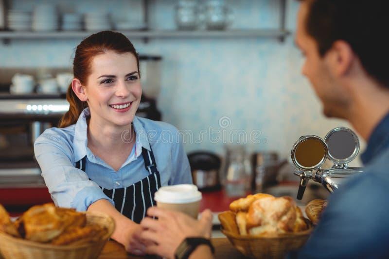Café de oferecimento do barista feliz ao cliente no café imagens de stock royalty free