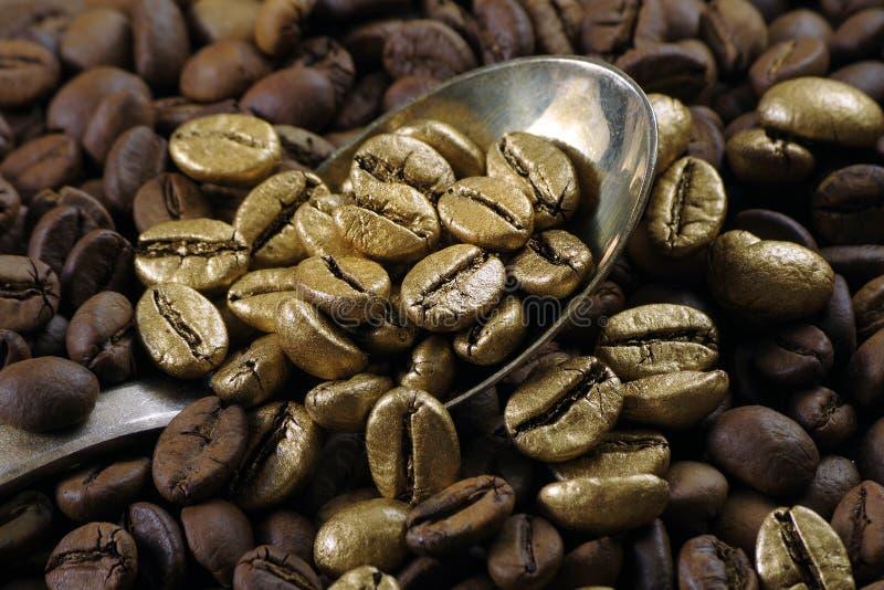 Café de ouro numa pilha de grãos de café O conceito de luxo é extraordinário Café em uma colher Café dourado imagem de stock royalty free