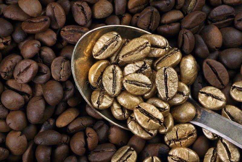 Café de ouro numa pilha de grãos de café O conceito de luxo é extraordinário Café em uma colher Café dourado imagens de stock royalty free