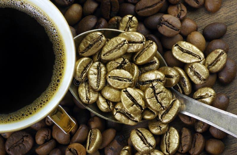 Café de ouro numa pilha de grãos de café O conceito de luxo é extraordinário Café em uma colher Café dourado foto de stock
