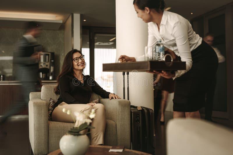 Café de portion de personnel de salon d'affaires au voyageur féminin photographie stock libre de droits
